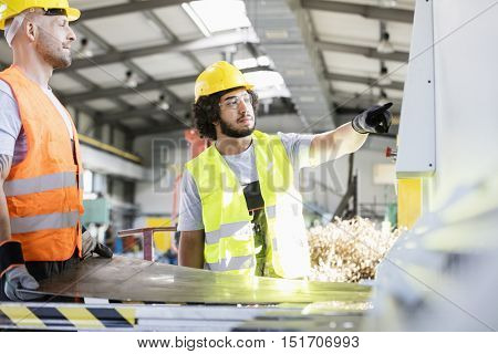 Male manual workers manufacturing sheet metal at factory