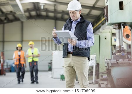 Mature male inspector writing on clipboard while workers in background at factory
