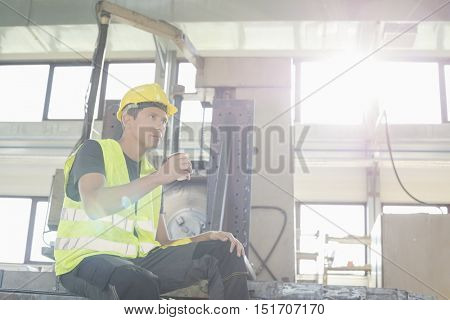 Low angle view of mid adult manual worker having coffee in metal industry