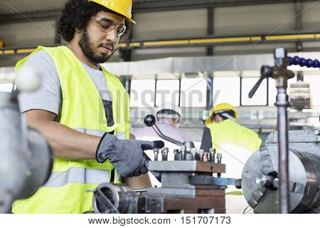 Young manual worker operating machinery in metal industry