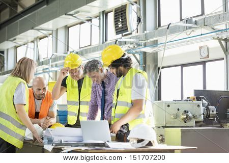 Male architect and manual workers discussing over blueprints in industry