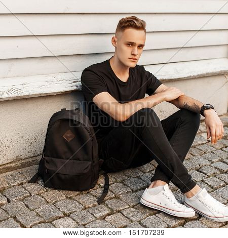 Young Handsome Guy In A Trendy Black Dress And White Shoes Sitting Near Wooden Wall. Black Backpack.
