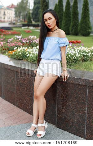 Beautiful Young Girl With Long Black Hair In A Summer Blouse And White Shorts Near The Flowers.