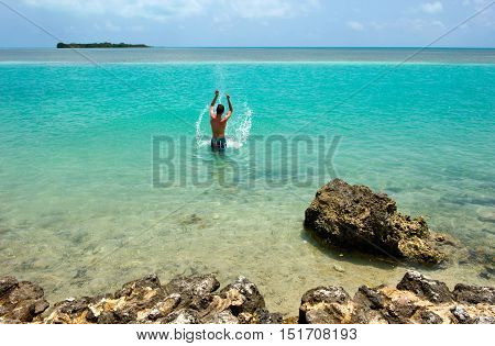 A teenager is playing in the water on a beach of the Florida Keys