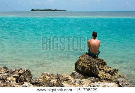 A teenager is sitting on a rock on a beach of the Florida Keys