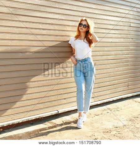 Beautiful Girl In A White T-shirt, High Waist Jeans And White Shoes Standing Near A Wooden Wall