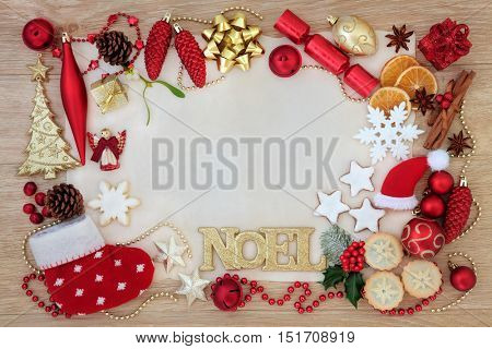 Christmas abstract background border with noel sign, tree decorations and baubles, gingerbread biscuits, orange and cranberry fruit, mince pies and spices on parchment paper over oak wood.