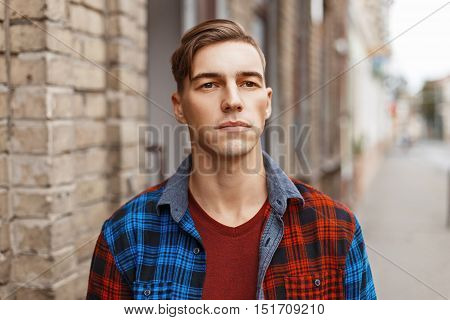 Portrait Of A Beautiful Young American Guy With Hairstyle Near The Brick Vintage Building.