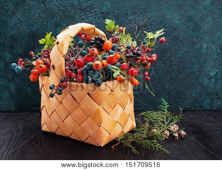 Wicker basket with wild berries on texture background with copy space