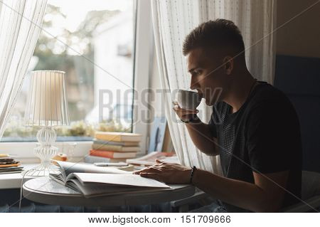 Young Man Rest In A Restaurant, Reading A Book And Drinking Coffee.