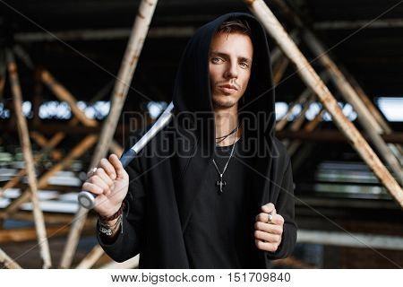 Angry Man In Black Clothes Holding A Bat On The Background Of Metal Pipes