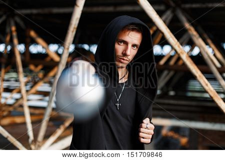 Aggressive Man Beats The Bat. Stylish Guy In Black Clothes With A Hood.