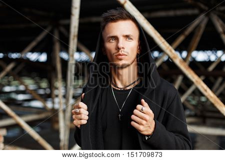 Handsome Stylish Man In Black Fashionable Clothes With A Hood Posing Against A Background Of Metal C
