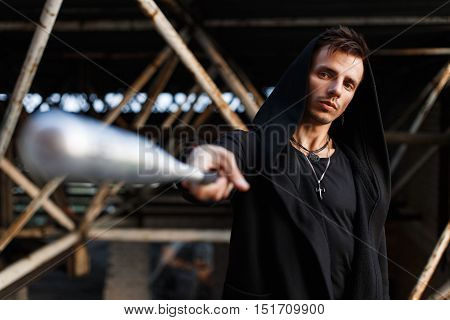 Serious Man In Black Clothes With A Hood Holds A Bat.