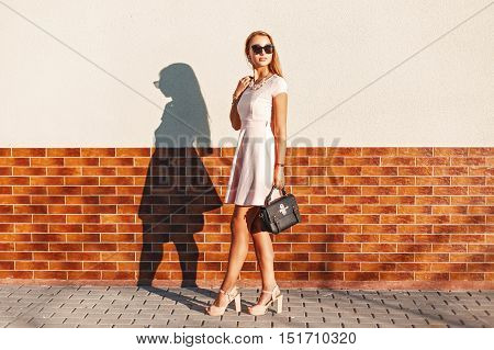 Stylish Young Girl In Sunglasses In A Pink Skirt With A Black Bag Near Brick Wall.