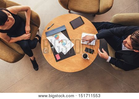 Young Businessman And Woman Meeting In Office Lobby