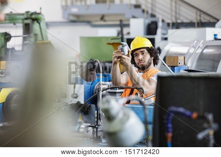 Young manual worker examining metal in factory