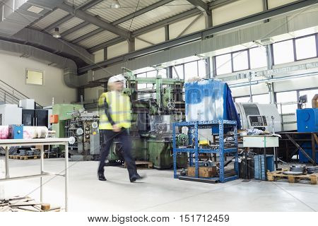 Blurred motion of male supervisor walking in metal industry