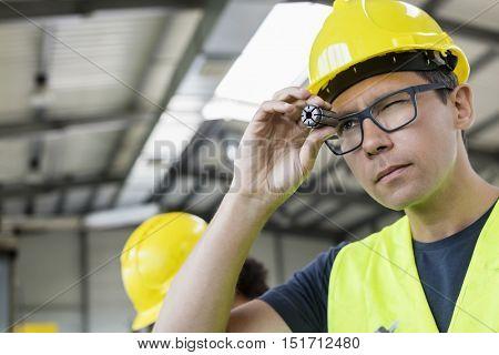 Mid adult manual worker examining metal in industry