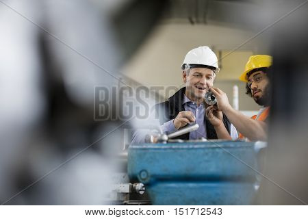 Male supervisor with worker examining metal in industry
