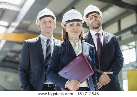Portrait of mature businesswoman with male colleagues in metal industry
