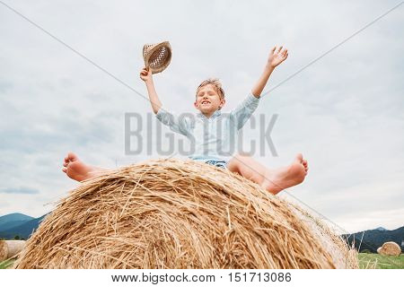 Happy boy sits over big rolling haystack