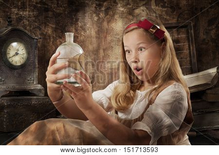 Portrait of a beautiful young girl expresses wonder holding the magic potion in her hands dressed as Alice in Wonderland indoor