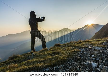 Hiker Taking The Picture The Sunrise In The Mountains.