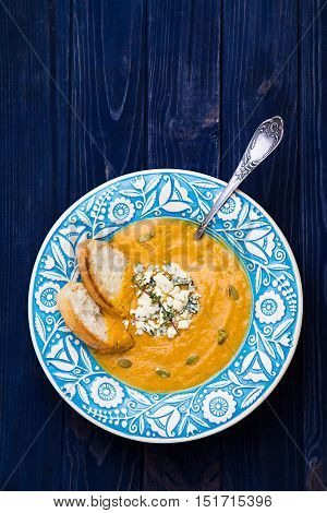 Creamy squash soup in blue dish with blue cheese, thyme and pumpkin seeds on navy background top view