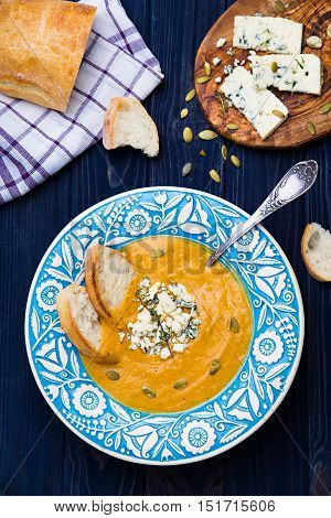 Creamy squash soup with blue cheese, bread slices, thyme and pumpkin seeds on navy blue background top view