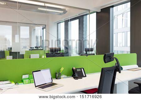 Laptop and landline phone on desk at office