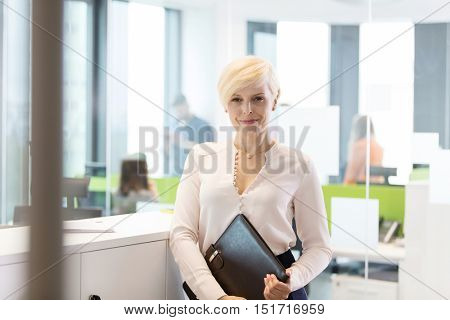 Portrait of confident mature businesswoman with file in office
