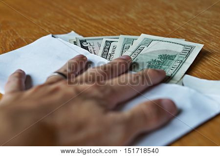 Male hand holding its fingers on white envelope full of American Dollars (USD, US Dollars) on the wooden table as a symbol of illegal cash transfer or bribery (black market or gray economy)