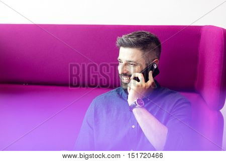 Smiling mid adult businessman talking on mobile phone while sitting on purple couch at office