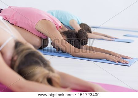 Young women having a stretching class on foam pads
