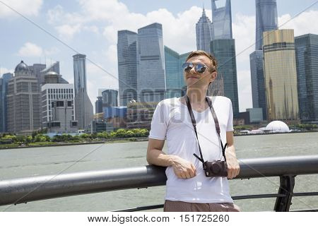Thoughtful man leaning on railing against Shanghai World Financial Center