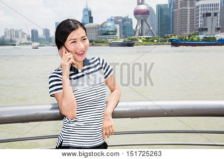 Happy young woman using smart phone while leaning on railing against Oriental Pearl Tower