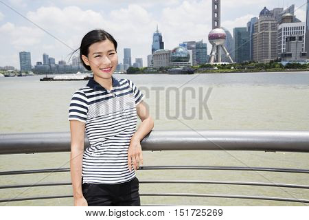 Portrait of woman leaning on railing by river with Oriental Pearl tower in background