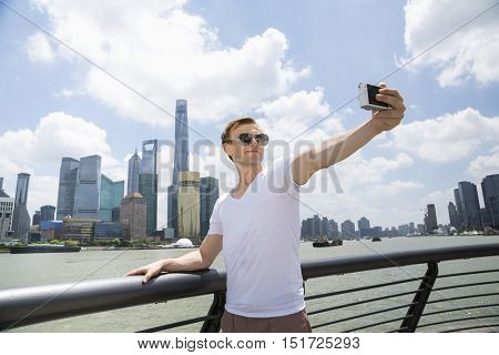 Man wearing sunglasses while taking selfie against Pudong skyline
