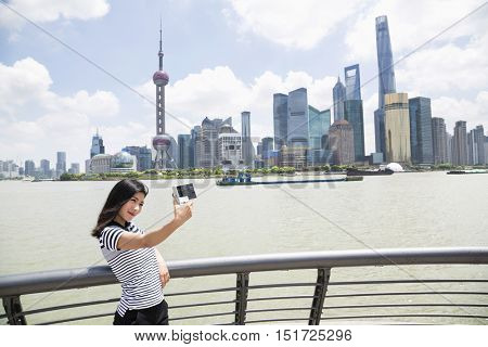 Young woman taking selfie while standing by railing against Pudong skyline