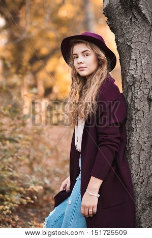 Beautiful teen girl 14-16 year old wearing stylish autumn clothes in park. Looking at camera.
