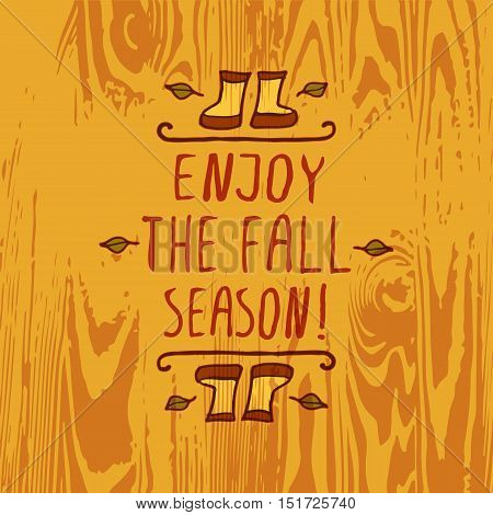 Hand-sketched typographic element with rubber boots, leaves and text on wooden background. Enjoy the fall season