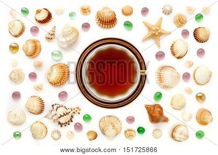 Cup of tea seashells and glass beads on a white background. The view from the top