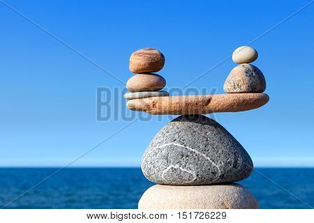 Concept of harmony and balance. Balance stones against the sea. Rock zen in the form of scales