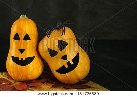 Halloween pumpkins with scary faces and ruber spider on dark background horizontal orientation