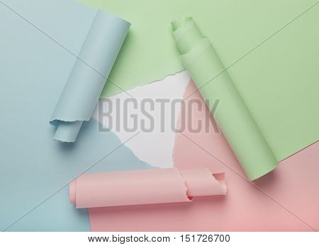 Three pieces of torn, colorful paper forming abstract background