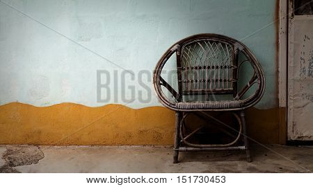 Wicker armchair with old wall background, vintage style