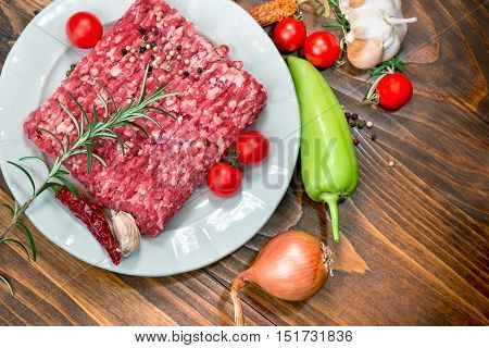 Fresh raw minced beef - ground beef on white plate and vegetables