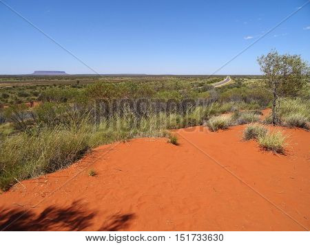 View desert plains of the Outback, Northern Territory, Australia. In the background, on the horizon line, there is the Mount Conner, also known as Connor, Attila and Artilla.