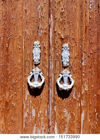 weathered door with door knockers in a typical Portugese house in Tavira Portugal